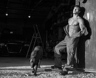 Muscular guy with black dog Royalty Free Stock Photography