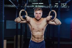 Muscular guy doing exercise on the rings Crossfit style Stock Photos