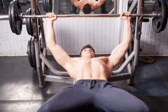 Muscular guy doing exercises in the gym Royalty Free Stock Images
