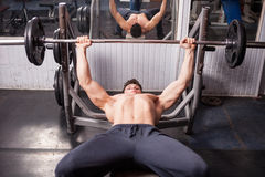 Muscular guy doing exercises in the gym Royalty Free Stock Photo