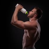Muscular guy drinking water after training Royalty Free Stock Photos