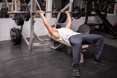 Muscular guy exercising in the gym Royalty Free Stock Photo