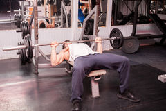 Muscular guy exercising in the gym Royalty Free Stock Image