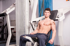 Muscular guy exercising in the gym Stock Photography
