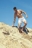 Muscular guy goes down the slope in shorts. Handsome muscular guy goes down the slope in shorts Stock Photos