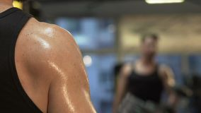Muscular guy lifting big dumbbells in front of mirror, active workout in gym. Stock footage stock video footage