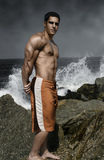 Muscular guy by the ocean. Muscular guy on the rocks by the ocean Stock Photography