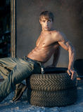 Muscular guy. Portrait of handsome young muscular shirtless man with rubber tyres Royalty Free Stock Images