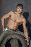 Muscular guy. Portrait of handsome young muscular shirtless man with rubber tyres Stock Photo