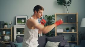 Muscular guy in sportswear boxing alone indoors in apartment enjoying activity. Muscular guy in sportswear is boxing alone indoors in apartment enjoying activity stock video