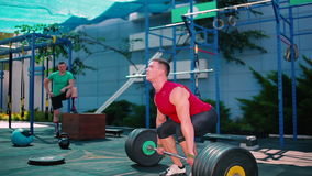Muscular guy training with barbell outdoor stock video