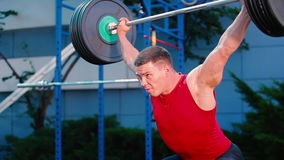Muscular guy training with barbell at the sports ground stock video