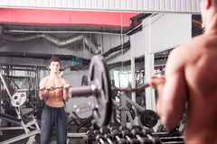 Muscular guy working out in the gym. Lifting heavy weights. Bodybuilder workout Stock Photography