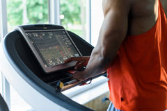 Muscular handsome black man jogging on a treadmill in the gym Stock Images