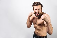Muscular and handsome guy is standing in a defence position. He is ready to fight or defence himself. Man looks very stock photos