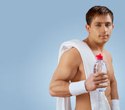 A muscular handsome man with bottle of water Royalty Free Stock Images