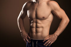 Muscular Handsome Man. Demonstrates His Abdominal Muscles On Brown Background stock photo