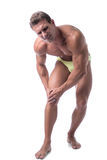 Muscular handsome man holding his leg and knee in Stock Images