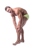 Muscular handsome man holding his leg and knee in Royalty Free Stock Photography