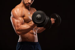 Muscular handsome man is training with dumbbells in gym. isolated on black background with copyspace Royalty Free Stock Photo