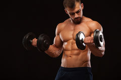 Muscular handsome man is training with dumbbells in gym. isolated on black background with copyspace Stock Photography