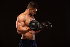 Muscular handsome man is training with dumbbells in gym. isolated on black background with copyspace Royalty Free Stock Images