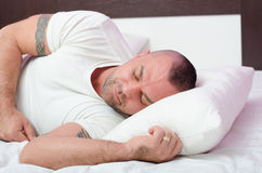Muscular handsome young man with arm tattoos sleeping peacefully. Muscular handsome young man with arm tribal tattoos sleeping peacefully in home bed stock photo