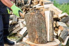 Muscular handsome young man in paint spattered jeans, sneakers and a bare chest standing chopping logs with an axe on a grey stock photography