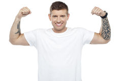 Muscular handsome young man showing his biceps Royalty Free Stock Images
