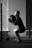 Muscular hard working man squatting with a med ball Stock Images
