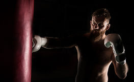 Muscular hipster fighter giving a forceful kick during a practise with a boxing bag. Stock Images
