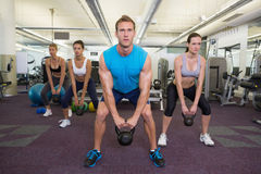 Muscular instructor leading kettlebell class Stock Photo