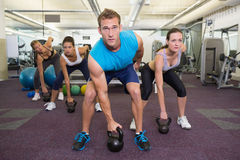 Muscular instructor leading kettlebell class Royalty Free Stock Photo