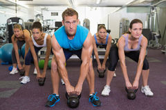 Muscular instructor leading kettlebell class Royalty Free Stock Photos