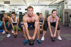 Muscular instructor leading kettlebell class Stock Photography