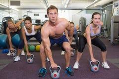 Muscular instructor leading kettlebell class Stock Photos