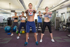 Muscular instructor leading kettlebell class Stock Images