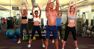 Muscular instructor leading kettlebell class stock video footage