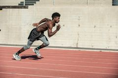 Track workout to maintain discipline. Muscular Jamaican athlete leaning forward for momentum while sprinting at stadium stock images