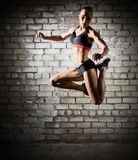 Muscular jumping woman on brick wall (dark version) Stock Image