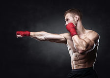Muscular kickbox or muay thai fighter punching. Royalty Free Stock Photos