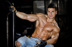 Muscular latino bodybuilder in jeans hanging from metal handle Royalty Free Stock Photos