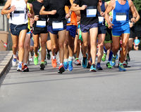 Muscular legs of athletes running the marathon on the city stree Royalty Free Stock Images