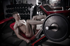 Muscular legs. Handsome bodybuilder workout on trainer in the gym Royalty Free Stock Photos