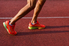 Muscular legs of man in sneakers on running track Royalty Free Stock Photos