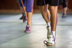 Muscular legs with a resistance band. Sports muscular legs with a resistance band,  exercising at gym Stock Photography