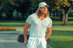 Muscular long-haired guy in sunglasses with skateboard Stock Image