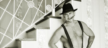 Muscular macho in a felt hat Stock Images