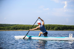 Muscular male athlete in a canoe rowing Royalty Free Stock Images