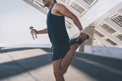 Muscular Male athlete sprinter doing stretching exercise, exercising outdoors, jogging outside. healthy lifestyle. Muscular Male athlete sprinter doing stock images